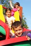De kinderen spelen in de speelplaats Stock Afbeeldingen
