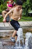 De kinderen spelen in de waterfontein Stock Afbeelding