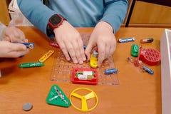 De kinderen spelen een elektromechanische aannemer Edukatsiya groeiende generatie Elektro kringen Multi-colored speelgoed voor stock afbeeldingen