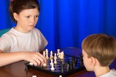 De kinderen spelen een raadsspel genoemd schaak Stock Foto