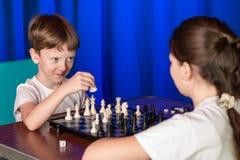 De kinderen spelen een raadsspel genoemd schaak royalty-vrije stock afbeeldingen