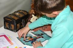 De kinderen spelen een zoektocht, schatborst, open ijzerslot, spel, vermaak, pretpark, rolspel, team, raadsel, logicaspel, stock foto