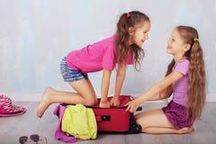 De kinderen spelen en lachen met een koffer Stock Foto's