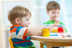 De kinderen spelen en schilderen thuis of kleuterschool of playschool Royalty-vrije Stock Afbeeldingen