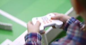 De kinderen spelen in spelen gebruikend het spelcontrolemechanisme Draadloos spel controler stock footage