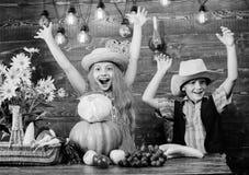 De kinderen spelen groenten houten achtergrond De hoed van de de jongensslijtage van het jonge geitjesmeisje viert de rustieke st royalty-vrije stock foto's