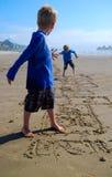 De kinderen spelen Hinkelspels op Strand stock fotografie