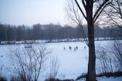 De kinderen spelen ijshockey op een bevroren meer royalty-vrije stock afbeelding