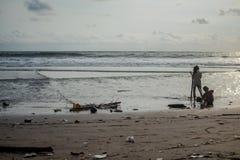 De kinderen spelen met afval op het strand ecologig wereldwijd probleem, plastiek aangaande het strand royalty-vrije stock afbeelding