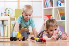 De kinderen spelen met houten trein en bouwen stuk speelgoed spoorweg thuis, kleuterschool of opvang Stock Foto