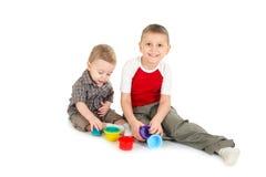 De kinderen spelen met kleurenspeelgoed. Stock Afbeeldingen