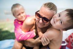 de kinderen spelen met moeder op het strand stock foto's