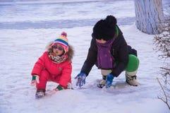 De kinderen spelen met sneeuw Stock Afbeeldingen