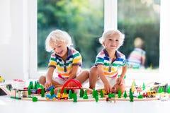 De kinderen spelen met stuk speelgoed trein Jonge geitjes houten spoorweg Royalty-vrije Stock Afbeelding