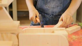 De kinderen spelen op ambachtworkshop Close-up van meisje het hameren spijkers wordt geschoten die Aanbiddelijk meisje in jeans 4 stock video