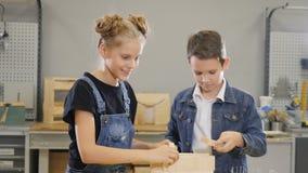 De kinderen spelen op ambachtworkshop Leuk weinig jongen en zijn school-verouderde zuster die met houten half afgewerkte stukken  stock videobeelden