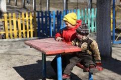 De kinderen spelen op de speelplaats Royalty-vrije Stock Afbeeldingen