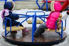 De kinderen spelen op de speelplaats in de winter Royalty-vrije Stock Foto's