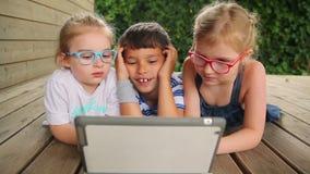 De kinderen spelen op de tablet stock video