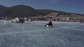 De kinderen spelen op het ijs op een opblaasbare ring Rubberring stock videobeelden