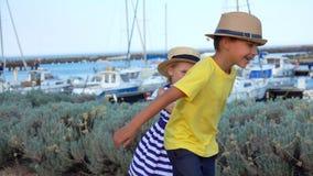 De kinderen spelen op de kade van de jachthaven stock videobeelden