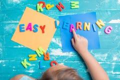 De kinderen spelen plastic brieven aan combinatieswoord ` het Gemakkelijke Leren ` stock foto's