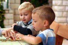 De kinderen spelen raadsspel stock foto