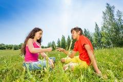 De kinderen spelen rots-papier-schaar op gras stock afbeeldingen
