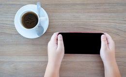 De kinderen spelen smartphone en hebben koffiekop stock afbeeldingen
