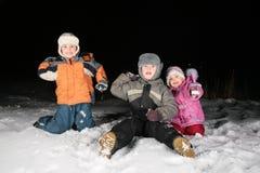 De kinderen spelen snowblls in de nacht Stock Afbeeldingen