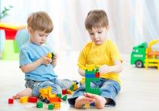De kinderen spelen speelgoed thuis op vloer Stock Afbeelding