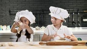 De kinderen spelen volwassen beroepen peuterkinderen in schorten en van chef-kokkappen kok in keuken thuis Thuis het koken stock videobeelden