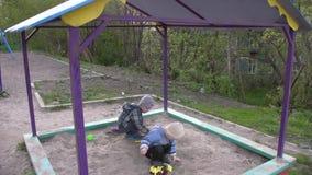 De kinderen spelen in de zandbak stock footage