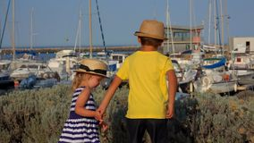 De kinderen springen op de kade van de jachthaven stock videobeelden