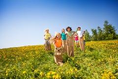 De kinderen springen in zakken terwijl samen het spelen stock afbeelding