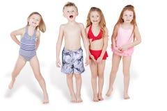 De kinderen in strandkostuums hebben pret Stock Foto's
