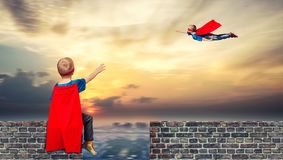 De kinderen in superherokostuums bewaken de orde in de stad royalty-vrije stock afbeeldingen