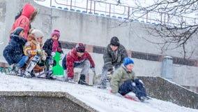 De kinderen tijdens de zware sneeuw en de wind, hebben pret het sledding stock afbeelding