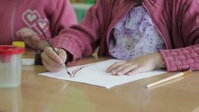 De kinderen trekken in kleuterschool op papier stock video