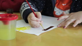 De kinderen trekken in kleuterschool op papier stock footage