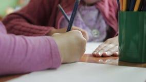 De kinderen trekken in kleuterschool op papier stock videobeelden