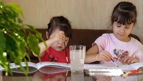 De kinderen trekken met kleuren Twee meisjes trekken huizen op de lijst met verven Een borstel wordt gewassen in een duidelijk gl stock footage