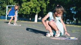 De kinderen trekt De meisjes trekken met krijt in het park stock videobeelden