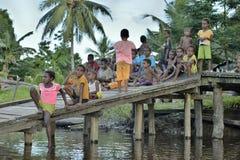 De kinderen van asmatmensen zitten op houten brug op de rivier Stock Fotografie