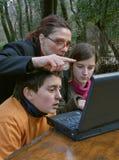 De kinderen van het vrouwenonderwijs bij laptop royalty-vrije stock foto's