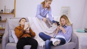 De kinderen van mammaaanbiedingen om een boek te lezen stock footage