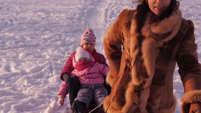 De kinderen van mammabroodjes op een slee stock footage