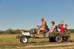 De kinderen van mensenbroodjes op een minitractor in koncha-Zaspa, de Oekraïne Stock Fotografie