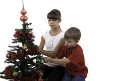De kinderen verfraaien een boom van het Nieuwjaar Royalty-vrije Stock Afbeeldingen