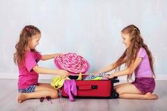 De kinderen verzamelen kleding in koffer Stock Foto